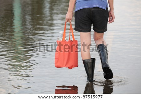 girl walking on flooded street,carrying fresh water for drinking. - stock photo