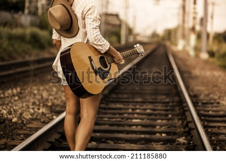 Girl walking on railway wish guitar