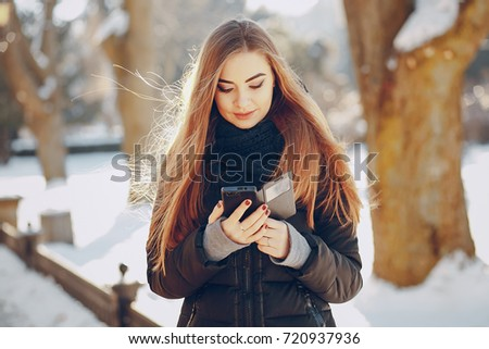 girl walking on snow-covered town, drinking coffee, photographed on the phone and riding on a sled #720937936