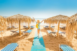 Girl walking on the beach with sunbeds and sun umbrellas. Seaside resort and summer vacation concept