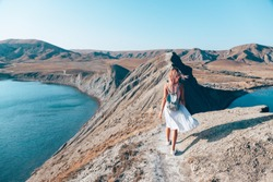 Girl walking on the mountain top over blue sea view
