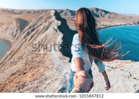 Girl walking on the mountain top over blue sea view. Follow me - POV. #1055847812