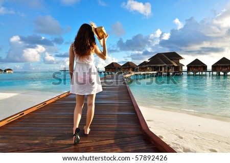 Girl walking on the pathway to spa house, Maldives