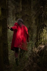 Girl walking through forest wearing bright red jacket by herself.