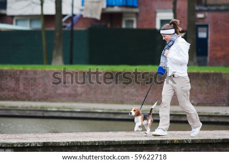 Girl walking with her dog on the leash. Beagle puppy