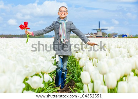 Girl walks between of the purple tulips field