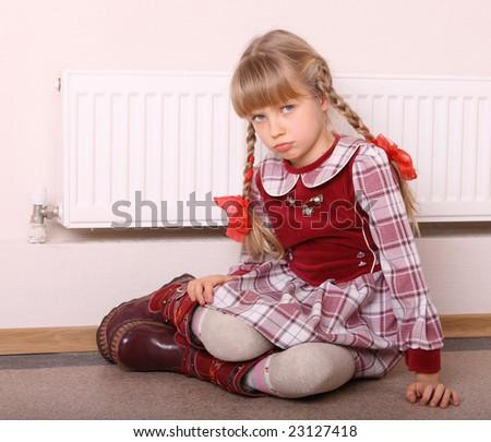 Girl  warm  near radiator.  Energy crisis.