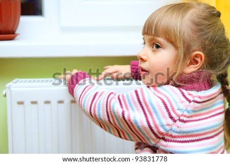 Girl warm one's hands near radiator at home.