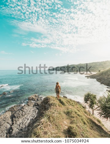 Girl watches the sunset in Kings beach, Byron Bay, Australia #1075034924