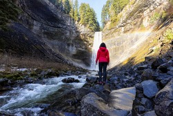 Girl watching a beautiful waterfall in Canadian Nature during winter. Taken in Brandywine Falls, near Whistler and Squamish, North of Vancouver, BC, Canada.