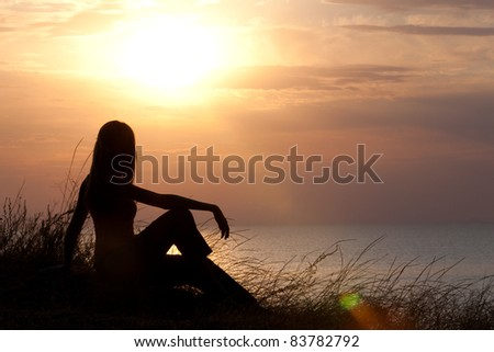 Girl watching sunrise on the grassy cliff