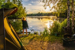 Girl watching sunset while  camping and fishing  by the lake .