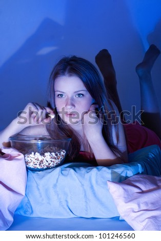 Girl watching television with popcorn
