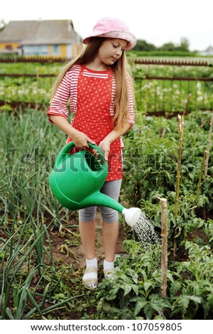 Girl watering plants in a kitchen-garden