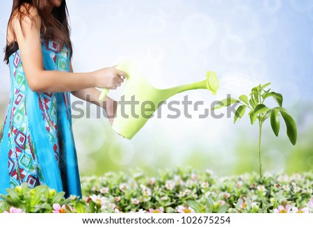 girl watering trees and flowers on a natural background