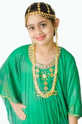 GIRL WEARING A TRADITIONAL ARABIC GREEN DRESS WITH GOLD EAR RING, HEAD AND NECK JEWELLERY.