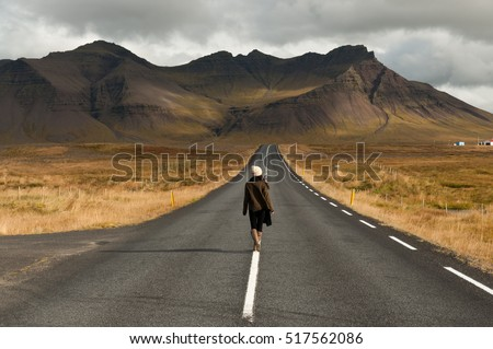 Girl wearing a woolly hat and wellington boots walks in the center of a quiet road towards a huge volcanic mountain in the distance, near Snaefellsjokull national park, Iceland.