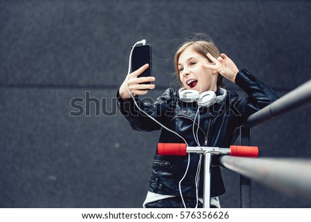 Girl wearing black leather jacket and white headphones standing on the scooter taking selfie with smart phone outdoor