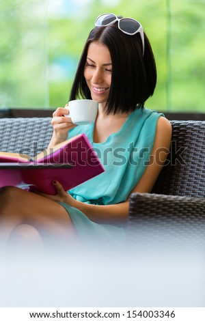 Girl wearing blue dress and sunglasses sits at the table of the cafe and reads book with cup of tea