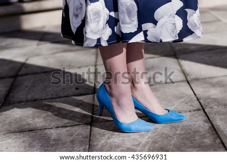 Girl wearing blue high heels shoes in the city, close up view