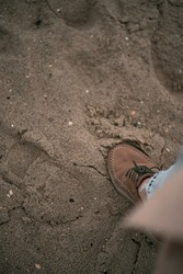 Girl wearing boots and jeans on the beach. Close up of human walking clothed on the sand beach during cold weather. Shoe on the beach sand. Fashionable and trendy  footwear.