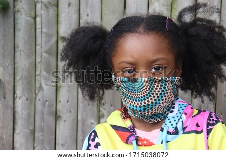 Girl Wearing Cloth Facemask outside wooden fence background stock photo