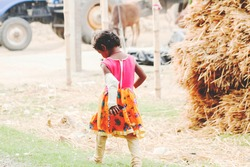 Girl wearing colorful clothes. Her hand is broken. A tractor and a cow in front of her in the blurry background. Copyspace. Alone little child on the road playing with her imagination. Childhood
