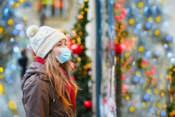 Girl wearing face mask on a Parisian street or at Christmas market looking at shop windows decorated for Christmas. Seasonal holidays during pandemic and coronavirus outbreak