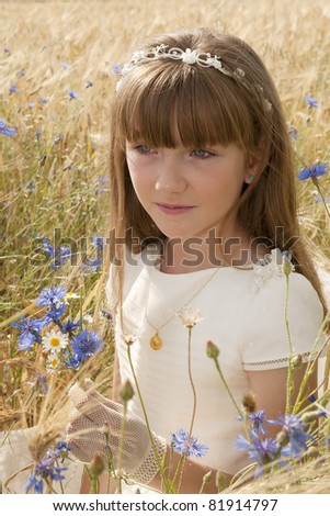 girl wearing first communion dress among the flowers and spikes