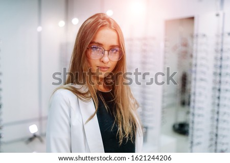 Girl wearing glasses. set of glasses in background in optical shop. Woman in spectacles. Eyesight correction.