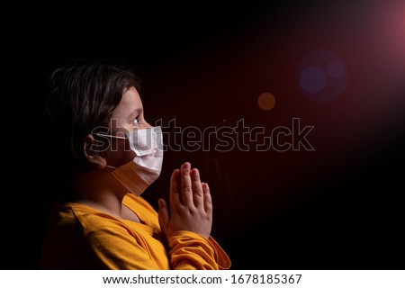 Girl wearing mask for protection against Covid-19 coronavirus pandemic. She is praying God for a cure and help. Copy space. Foto stock ©