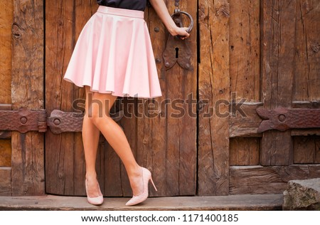Girl wearing nude colored skirt and high heel shoes