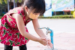 Girl wearing orange cloth face mask was washing her hands thoroughly with a tap, after cute child finished playing on playground. Keep children clean. Asian kids wearing a red dress is 4 years old.