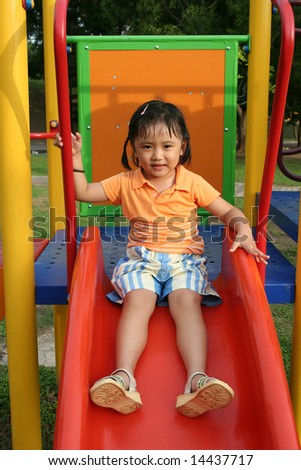 Girl wearing orange tee sitting on the slides in the park