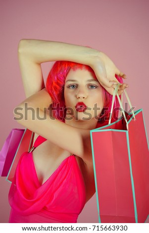 Girl wearing red wig and fashionable clothes. Woman with shopping bags. Fashion shopper making duck face on pink background. Sale and black friday. Holidays celebration concept. #715663930