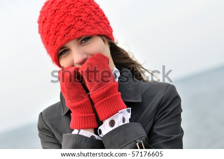 girl wearing  reg hat and red gloves outdoors