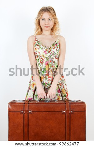 Girl wearing summer dress holds a vintage suitcase, anticipating travel.