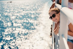 Girl wearing sunglasses standing at ship deck on a ferryboat and looking at the sea