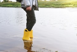girl wearing yellow rain boots standing in a river water. cropped view. unrecognizablelittle girl walking by the river bank in autumn season. fall concept.