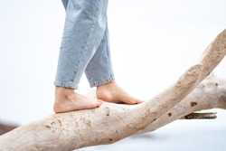 girl wears jeans, white background with focus on the forward foot