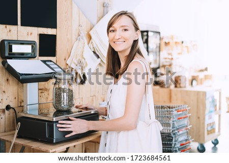 Girl weighs glass jar with hemp seeds. Woman with cotton bag chooses and buys products in zero waste shop. Weighing dry goods in plastic free grocery store. Sustainable shopping at local business