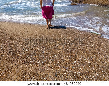 Girl wetting her feet in the sea. Beach with coarse sand and many shells.