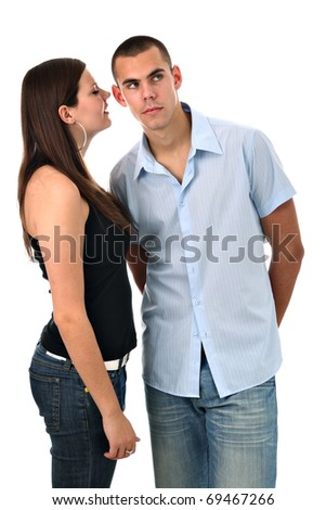 Girl whispers into her boyfriend's ear isolated on white