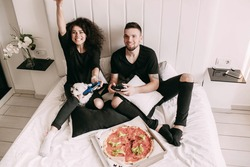Girl wins playing with man on PS on bed