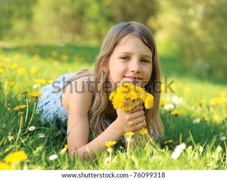 Girl wit a dandelions bouquet on green meadow