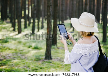 girl with a backpack walking in the woods.Travel by the forest. A young woman with a tablet stands at the tree. Smiling tourist looking for a way in the woods.