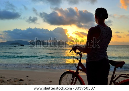 Girl with a bicycle on the beach admiring the beautiful sunset. Silhouette at twilight. Seychelles island La Digue