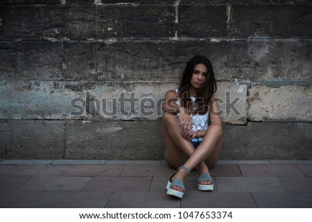 Girl with a black cap. Portrait of a girl on the background of the old wall. #1047653374