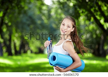 Girl with a bottle of water and gymnastic mats turn