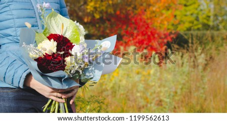 Girl with a bouquet of flowers in the autumn park as a concept of waiting for a romantic relationship. The photo may illustrate the fall. #1199562613